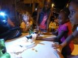 Annika watching the luckiest kitten in Gouyave enjoying some supper